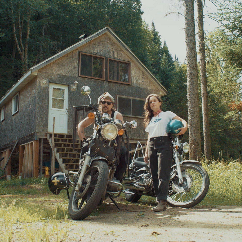 Le duo Ellemetue devant un chalet avec leur motos