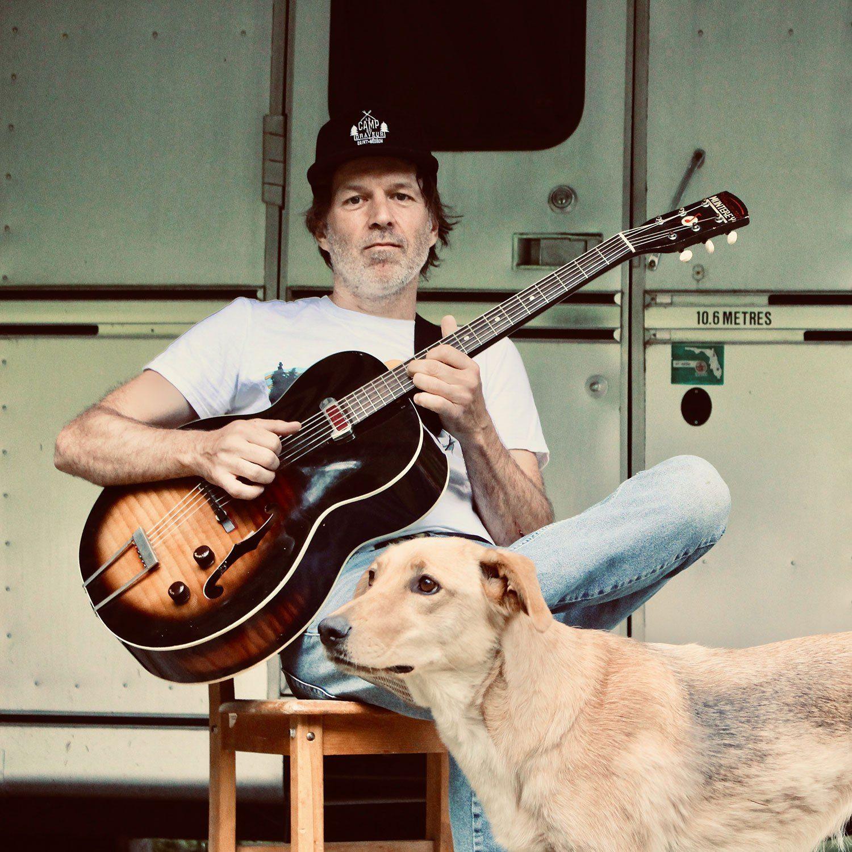 Fred Fortin avec une guitare et un chien