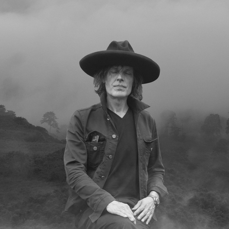 Jean Leloup en noir et blanc avec un grand chapeau